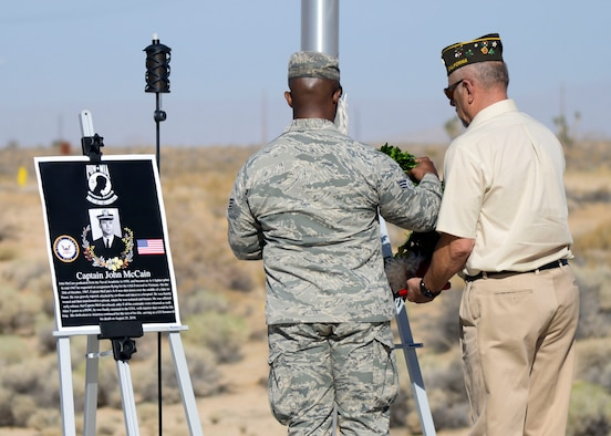 Staff Sgt. Matthew Buckner, 412th Training Wing Staff Judge Advocate's Office, and Army Veteran Joseph Antone, a member of the Veterans of Foreign Wars Post 9657, lay a wreath next to a photo of the late Sen. John McCain during a wreath-laying ceremony commemorating National POW/MIA Recognition Day at the Airman Leadership School Drill Pad at Edwards Air Force Base, California, Sept. 21. Prior to serving as U.S. Senate member, McCain served as a Navy pilot when he was shot down over Hanoi, Vietnam and held as a prisoner of war for more than five years. (U.S. Air Force photo by Giancarlo Casem)