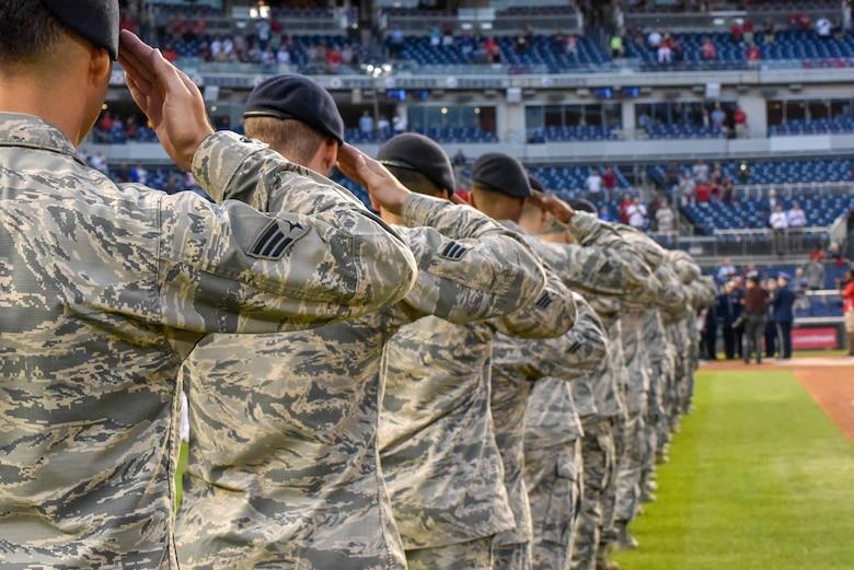 A line of Airmen salute.