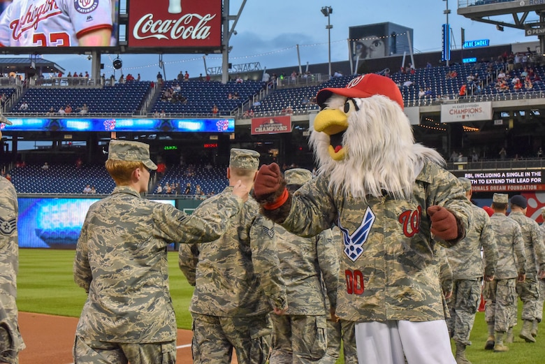 A mascot fist bumps an Airman.