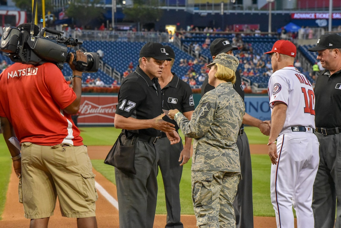 An Airman gives a card to a baseball official.