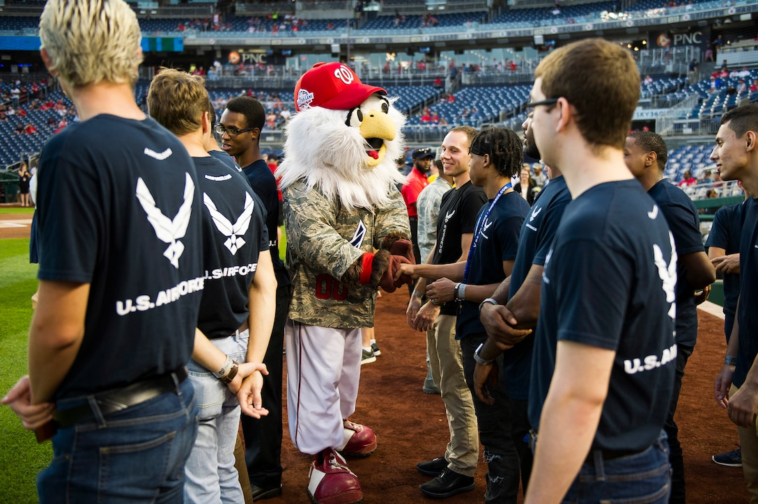 A mascot shakes hands with Airmen.