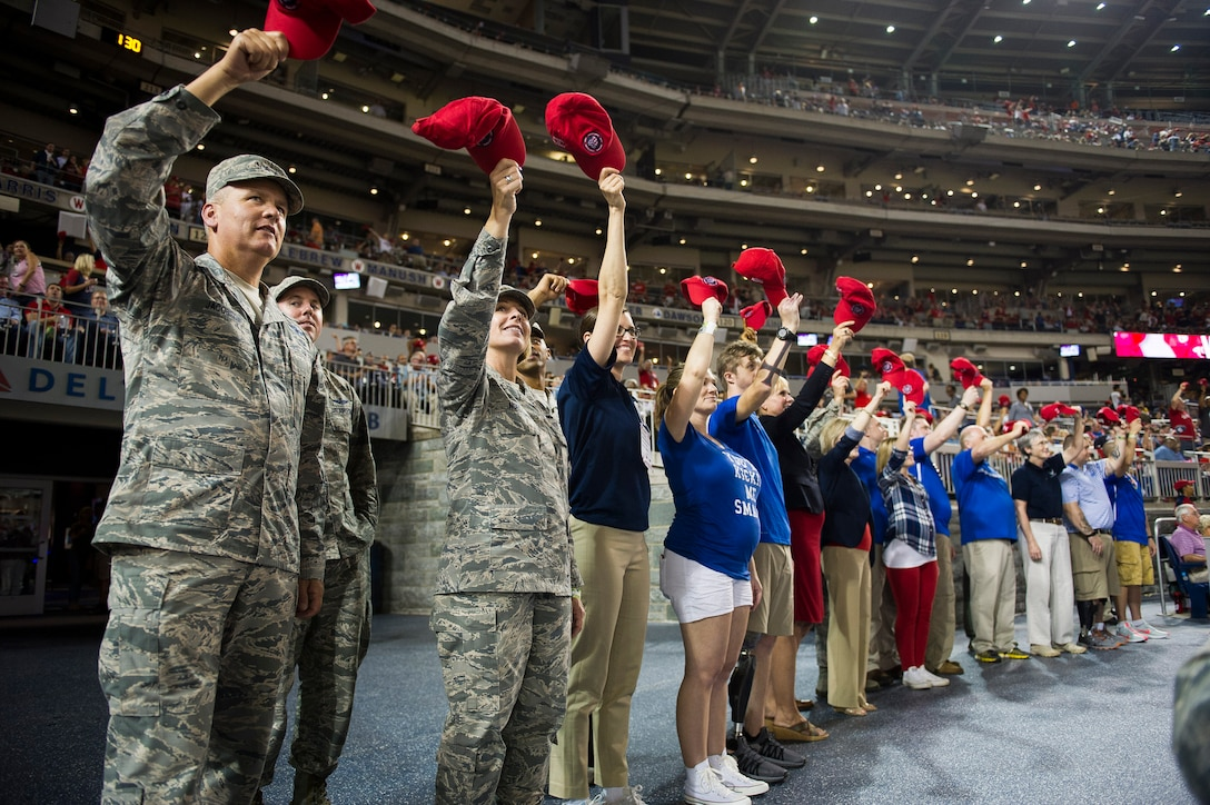 A group of Airmen and their families wave red hats to a crowd at the baseball game.