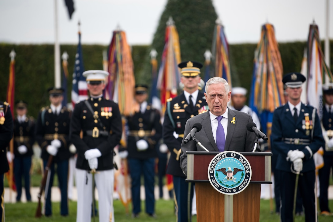 Defense Secretary James N. Mattis speaks at a lectern in front of troops on a parade field.