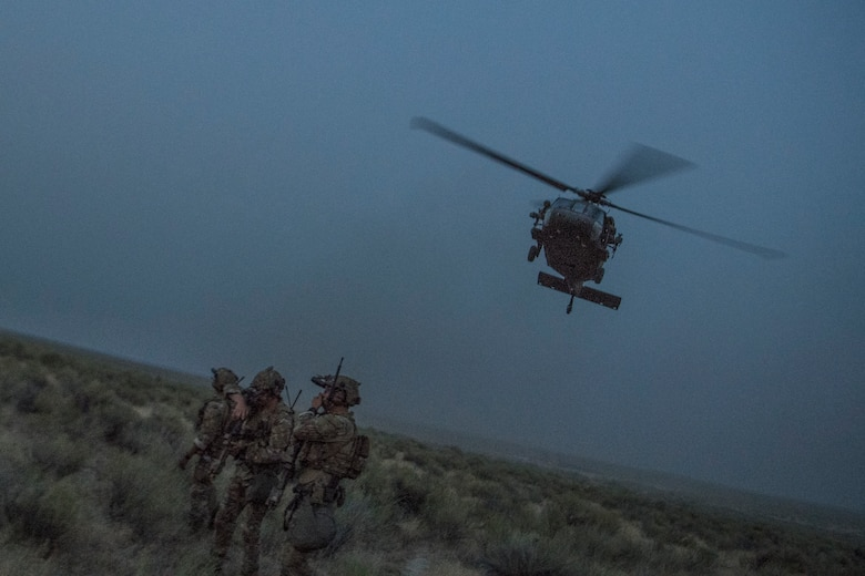An HH-60G Pave Hawk helicopter flies above Special Tactics Airmen with the 17th Special Tactics Squadron during Jaded Thunder at Mountain Home Air Force Base, Idaho, Aug. 20, 2018.
