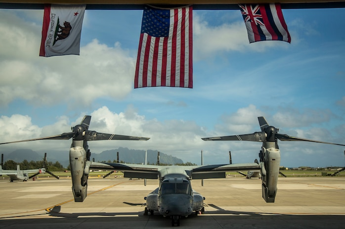 A static display of an MV-22B Osprey is showcased under the United States flag, flanked by the California and Hawaii state flags, symoblozing  Marine Tiltrotor Squadron 363's journey during the squadron's hangar dedication ceremony, Marine Corps Air Station Kaneohe Bay, Marine Corps Base Hawaii, Sept. 21, 2018. The dedication ceremony celebrated the arrival of Marines with VMM 363 and everyone that assisted in the construction of the hangar. The arrival of a second MV-22B Osprey squadron significantly increases Marine Aircraft Group 24's capability to respond to local emergencies within Hawaii and crises in the Indo-Pacific area of responsibility.