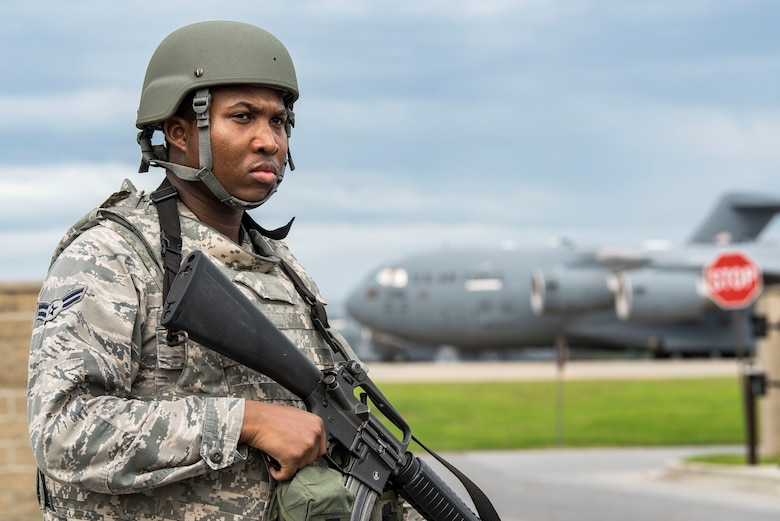 Airman 1st Class Denzel Gills, 9th Airlift Squadron aviation research management journeyman, stands guard near a flight line vehicle access gate Sept. 17, 2018, on Dover Air Force Base, Del. Gills was one of 34 Integrated Base Defense certified individuals who provided security for personnel and base assets during a two-day Force Protection/Major Accident Response Exercise. (U.S. Air Force photo by Roland Balik)