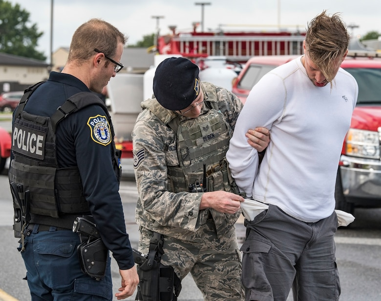 Justin Viens, supervisory police officer, observes Staff Sgt. Joshua Olsen, response force member, both assigned to the 436th Security Forces Squadron, as Olsen checks the pockets of a simulated vehicle gate runner and intoxicated driver involved in a motor vehicle accident Sept. 18, 2018, on Dover Air Force Base, Del. Tech. Sgt. Samuel Smolarek, 709th Airlift Squadron loadmaster, played the role of the driver while Viens used the exercise scenario to train Olsen on various field sobriety check methods during the base-wide Force Protection/Major Accident Response Exercise. (U.S. Air Force photo by Roland Balik)