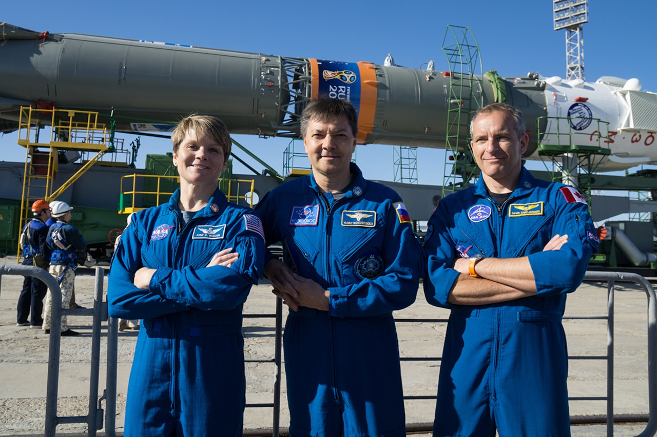 A U.S., Russian and Canadian astronaut pose in front of a Soyuz rocket.