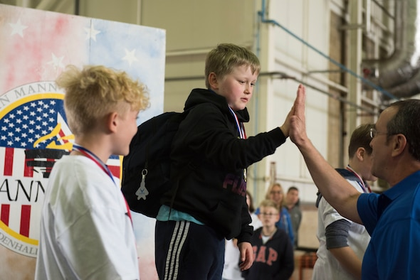 U.S. Air Force Chief Master Sgt. Clint Grizzell, 752nd Special Operations Group chief enlisted manager, high fives an athlete during the medal ceremony at the 37th Joan Mann Special Sports Day at RAF Mildenhall, England, Sept. 22, 2018.  Athletes from 28 local schools and organizations competed in 12 different sporting events, including the basketball shoot, obstacle course and football kick.  (U.S. Air Force photo by Senior Airman Lexie West)