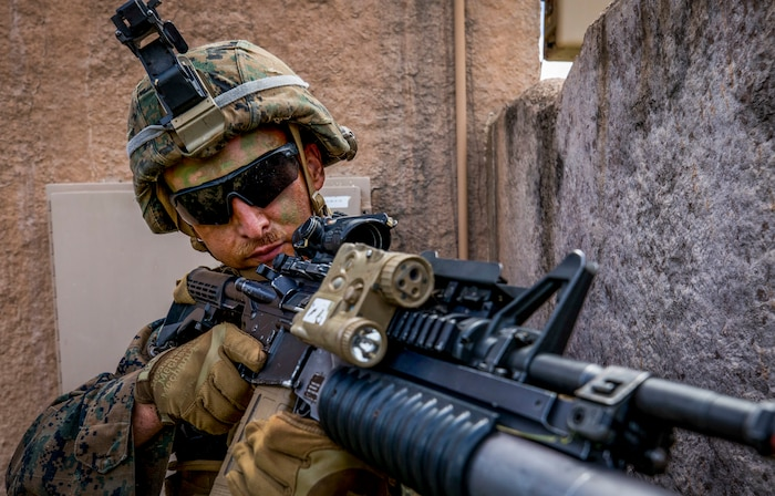 Lance Cpl. Michael Ziegenhals, a rifleman with India Company, 3rd Battalion, 3rd Marine Regiment, provides security during a village clearing drill part of a company level exercise at Marine Corps Training Area Bellows (MCTAB), Sept. 18, 2018. The company inserted into MCTAB with CH-53E Super Stallions to establish a secure landing zone, patrol over roads and through jungle terrain, and to clear simulated villages of hostiles.