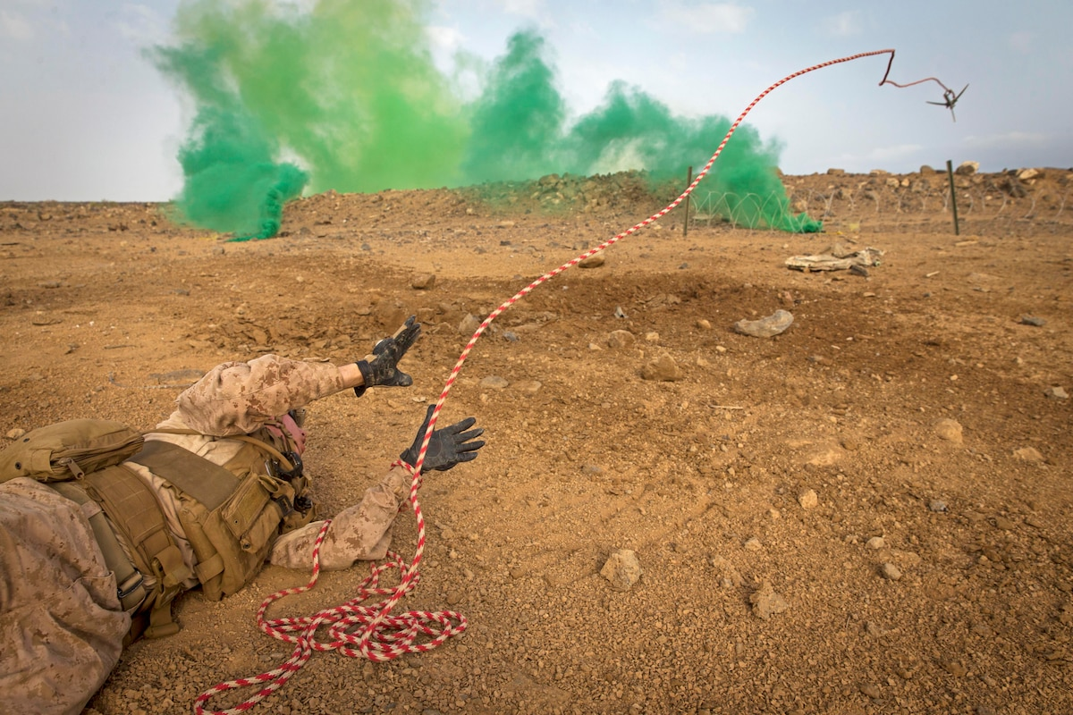 A Marine throws a hook from his position on the ground with green smoke in the foreground.