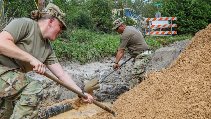 Soldiers use shovels to repair a road damaged by flooding in North Carolina.