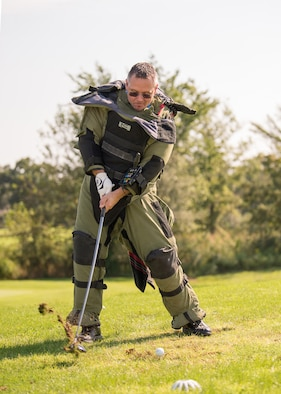 Lt. Col Jason Pennypacker, 512th Operations Group deputy commander, attempts to tee off while wearing an explosive ordnance disposal bomb suit at the Bluesuiters Golf Tournament Sept. 19, 2018, at the Eagle Creek Golf Course on Dover Air Force Base, Del. Teeing with the bomb suit was one of four special challenges set up throughout the 18-hole course.