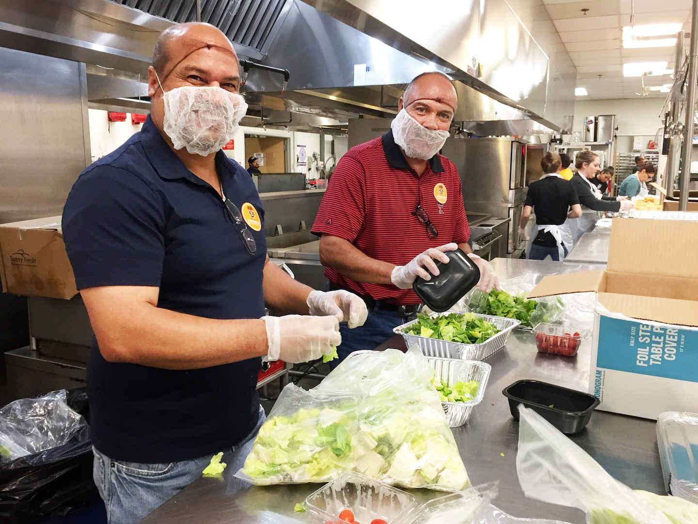 Two male employees wearing gloves prepare salads.