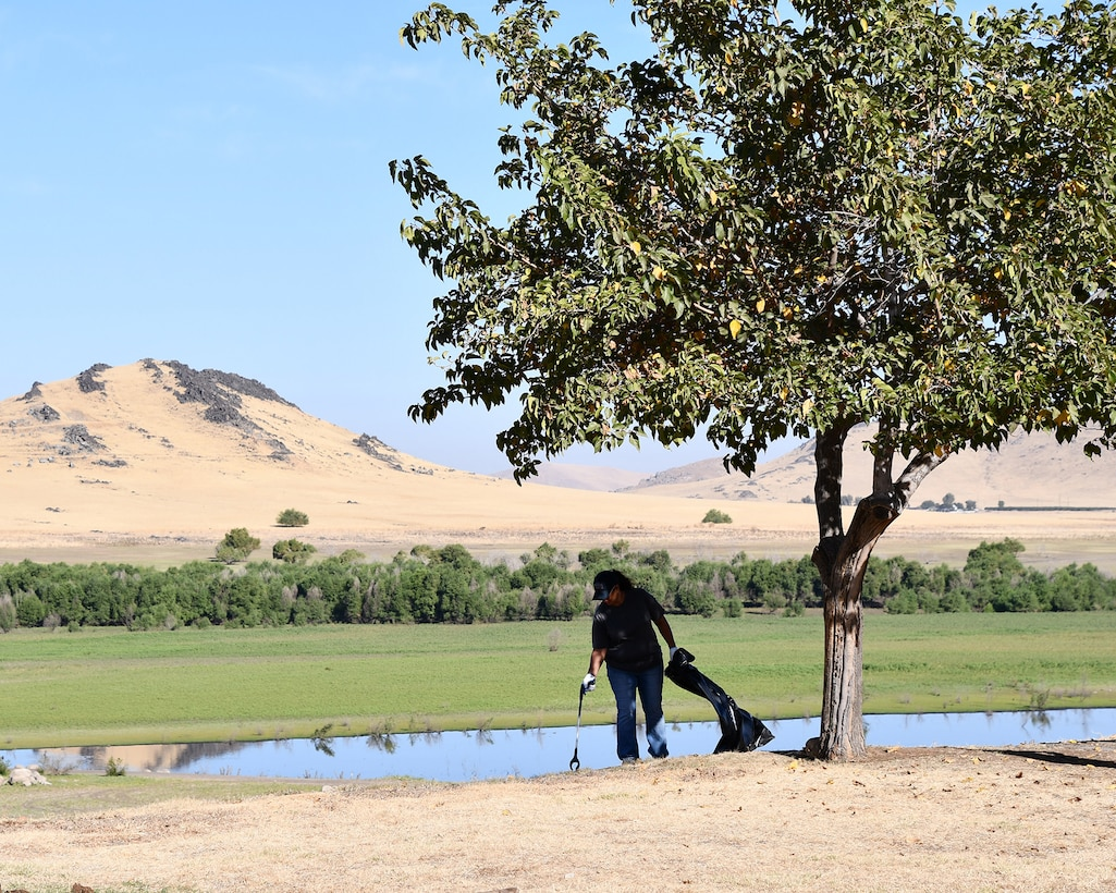 A volunteer picks up trash during a National Public Lands Day event held at the U.S. Army Corps of Engineers Sacramento District's Success Lake on September 22, 2018.