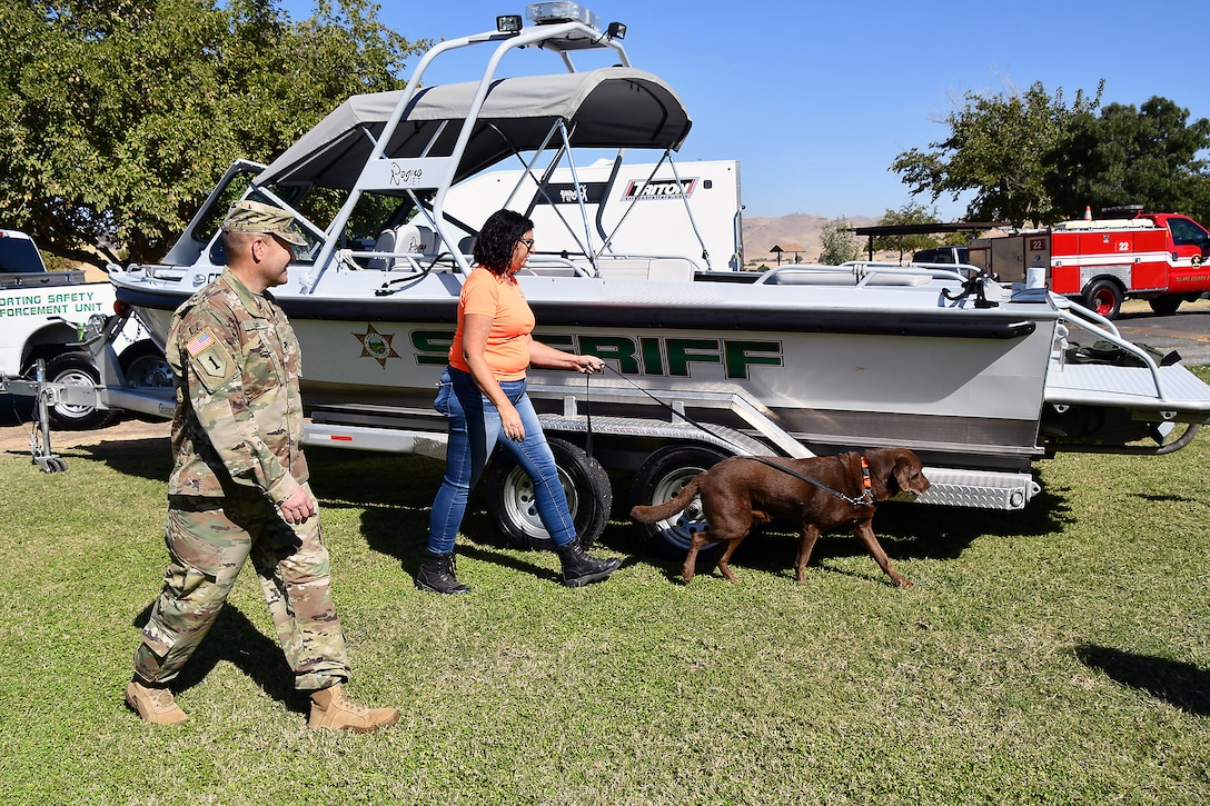 """Col. David Ray, commander U.S. Army Corps of Engineers Sacramento District, watches as Debi Johnson of Mussel Dogs demonstrates how quickly her chocolate lab """"Popeye"""" can find invasive species like quagga or zebra mussels on a boat. The demonstration was part of the National Public Lands Day event held at Success Lake on September 22, 2018."""