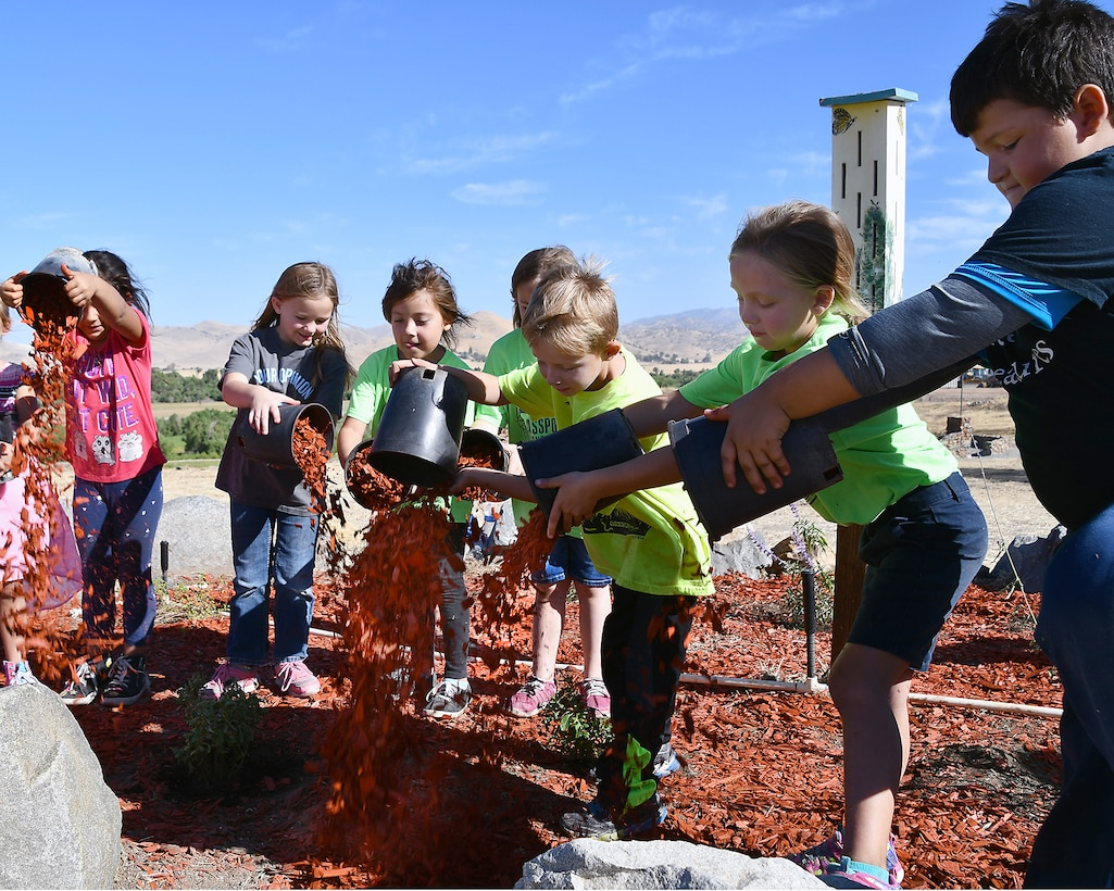 A group of young volunteers spread mulch while creating a Butterfly Garden at Success Lake during National Public Lands Day on September 22, 2018.
