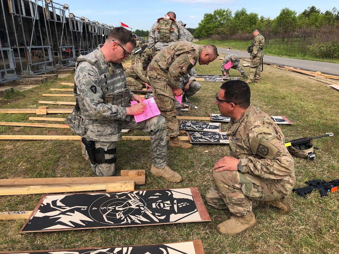 Maj Eric Manewal, 194th Wing, scores targets with Army personnel during the 47th Annual Winston P. Wilson Championship, Robinson Maneuver Training Center, Arkansas, May 1, 2018.  The annual events, hosted by the National Guard Marksmanship Training Center April 29-May 4, 2018, offer Servicemembers from the National Guard and international community an opportunity to test marksmanship skills in a battle-focused environment. (U.S. Air National Guard photo by Staff Sgt. Hope Funderburk)