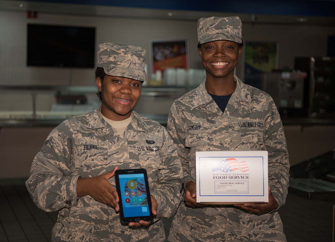 Airman 1st Class Latasha Blake, left, and Airman 1st Class Tashawnie Ormsby, 55th Force Suport Squadron Sustainment Services Flight food services journeymen, pose for a photo with a boxed meal and a tablet they use to view orders placed online through the new virtual Meal Ordering system Sept. 21, 2018, at Offutt Air Force Base, Nebraska. The new systems allows for faster service and more accessible ordering. (U.S. Air Force photo by Senior Airman Jacob Skovo)