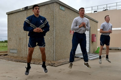 Airman Jake Peterson, Airman 1st Class Garrett Rivett and Airman Haden Stoner, 312th Training Squadron students, perform jump-squats during the Blood, Sweat and Stairs competition at the Louis F. Garland Department of Defense Fire Academy on Goodfellow Air Force Base, Texas, Sept. 22, 2018. Due to poor weather conditions, the coordinators removed the stair-climbing portion from the competition, and participants performed cardio-based exercises instead. (U.S. Air Force photo by Senior Airman Randall Moose/Released)