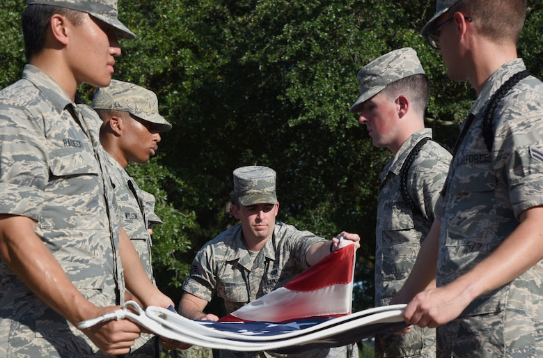 Keesler Airmen participate in folding the U.S. Flag during the POW/MIA Retreat Ceremony at Keesler Air Force Base, Mississippi, Sept. 20, 2018. The event was held to raise awareness and to pay tribute to all prisoners of war and those military members still missing in action. (U.S. Air Force photo by Kemberly Groue)