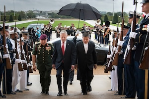 Defense Secretary James N. Mattis walks up steps with Malaysian Defense Minister Mohamad Sabu.