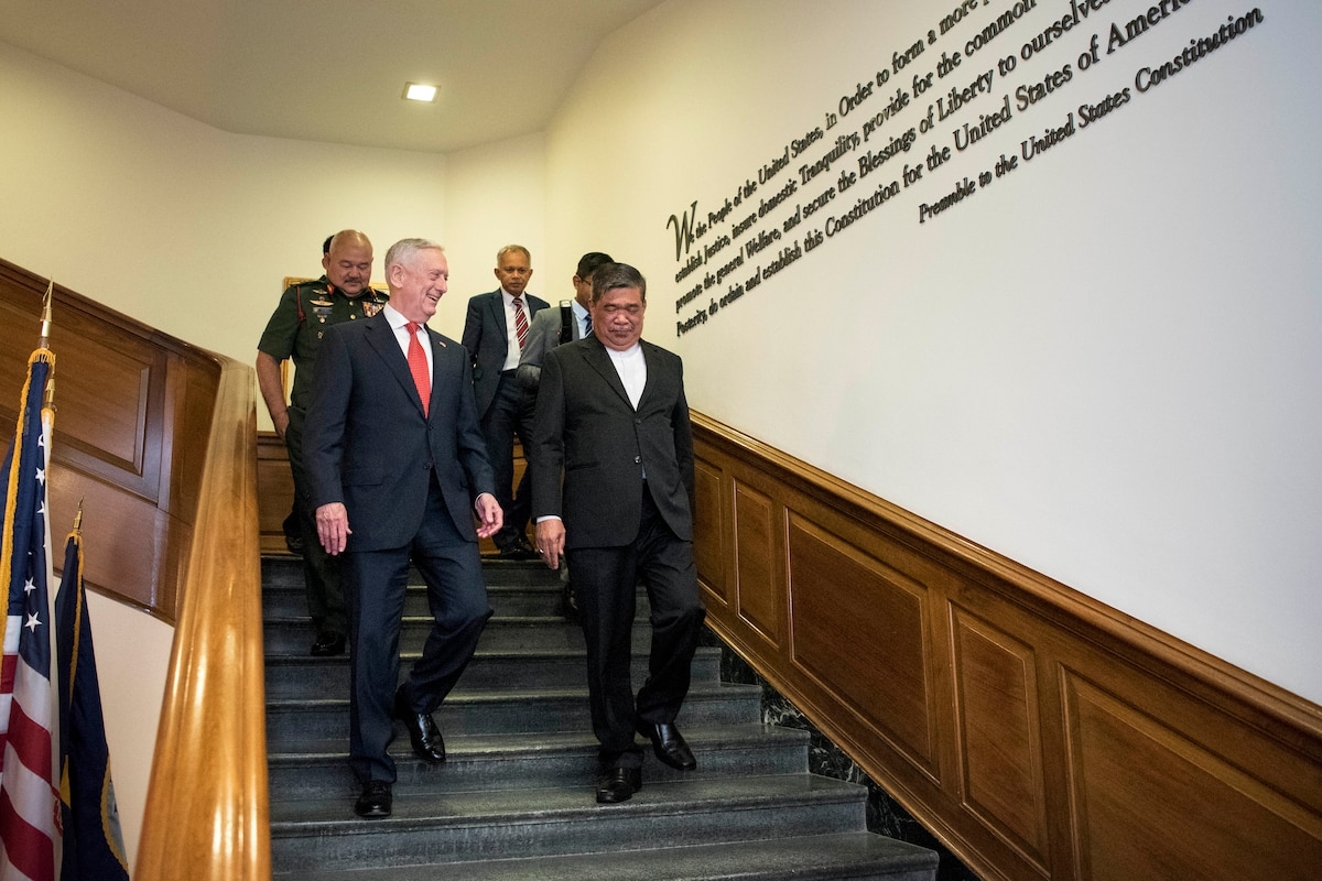 Defense Secretary James N. Mattis walks down steps with Malaysian Defense Minister Mohamad Sabu.