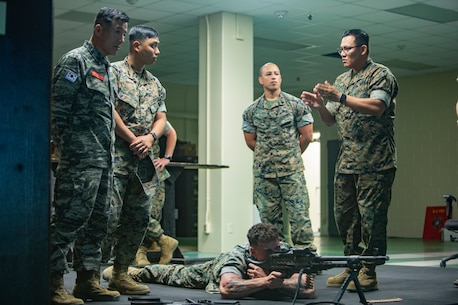 CAMP KINSER, Okinawa, Japan - Sgt. Maj. Jong Ik Jun, sergeant major of the Republic of Korea Marine Corps (far left) receives a brief on the Indoor Simulated Marksmanship Trainer (ISMT) program from Staff Sgt. Ryan W. Betonie (right), a marksmanship instructor for 3rd Marine Logistics Group, here, 20 Sept. Republic of Korea and United States Marine Corps forces are committed to the ironclad ROK-U.S. alliance and work together to further develop their partnership and combined capabilities. (U.S. Marine Corps photo by Lance Cpl. Armando Elizalde)