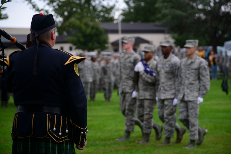 "A ceremonial bagpiper watches Dover Air Force Base Honor Guard members carry a folded American flag during a POW/MIA retreat ceremony Sept. 21, 2018, at Dover Air Force Base, Del. Bagpipers traditionally play ""Scotland the Brave"" or ""Amazing Grace"" during military ceremonies. (U.S. Air Force photo by Airman 1st Class Jonathan W. Harding)"