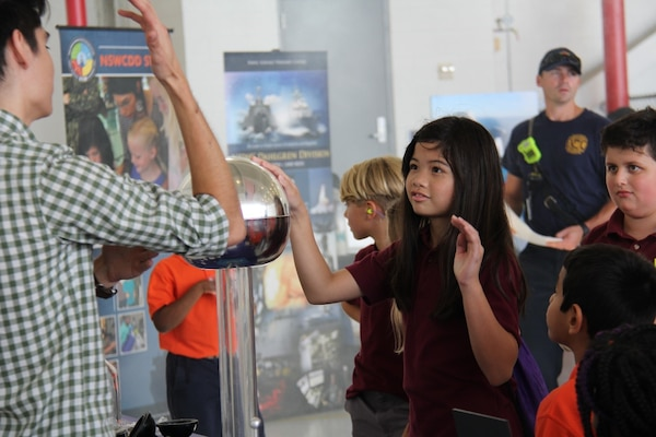 IMAGE: VIRGINIA BEACH, Va. (Sep. 21, 2018) - Virginia Beach elementary school students learn about static electricity from a Navy science, technology, engineering and mathematics (STEM) team at the annual NAS Oceana Air Show. The team of 30 STEM professionals from Naval Surface Warfare Center Dahlgren Division, NSWCDD Dam Neck Activity, and Dahlgren's Sly Fox program led education efforts through hands-on displays to fifth grade students throughout the air show.