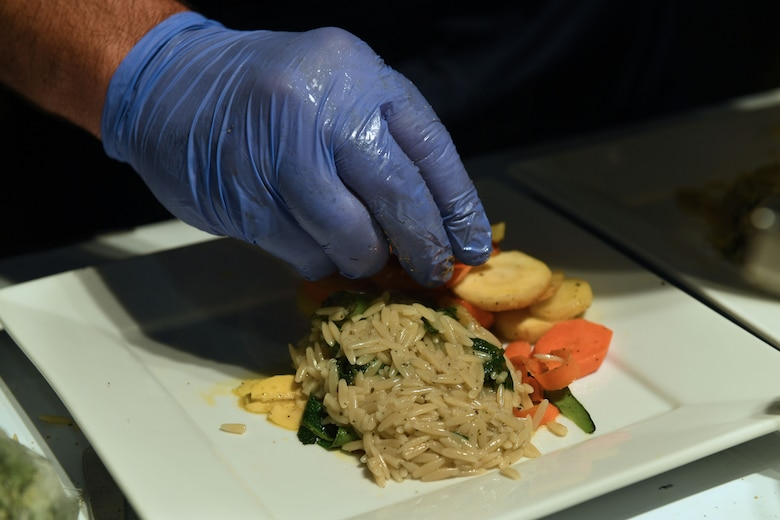 A hand places food on a plate.