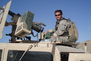 Soldier poses with gun on armored vehicle.