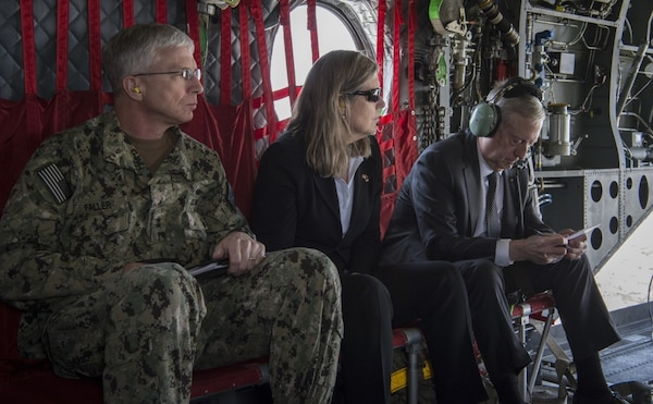 Admiral, civilian assistant and secretary of defense travel on a helicopter.