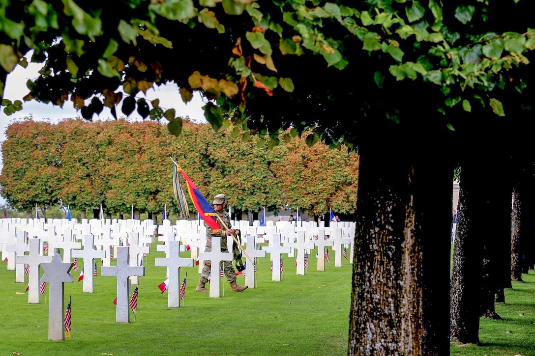 A service member walks between gravestones during a ceremony commemorating the St. Mihiel offensive of World War I.