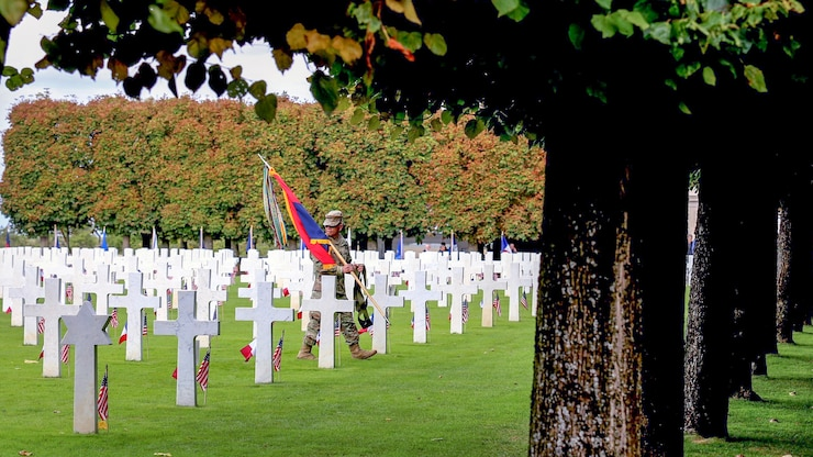 A Service member, walks between gravestones during a ceremony commemorating the St. Mihiel Offensive of World War I.