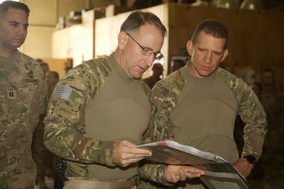 General and senior enlisted leader inspect soldiers' work.