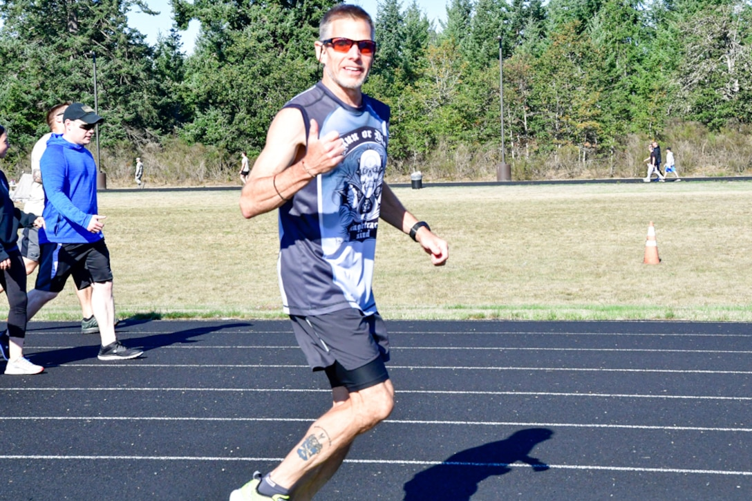 Bruce Robie, 225th Support Squadron National Airspace System Defense program manager, shows his enthusiasm for hitting mile 71 during the Joint Base Lewis-McChord 24-Hour POW/MIA Remembrance Run Sept. 19, 2018. Robie finished second in the individual standings with 74 miles. (U.S. Air National Guard photo by Maj. Kimberly Burke)