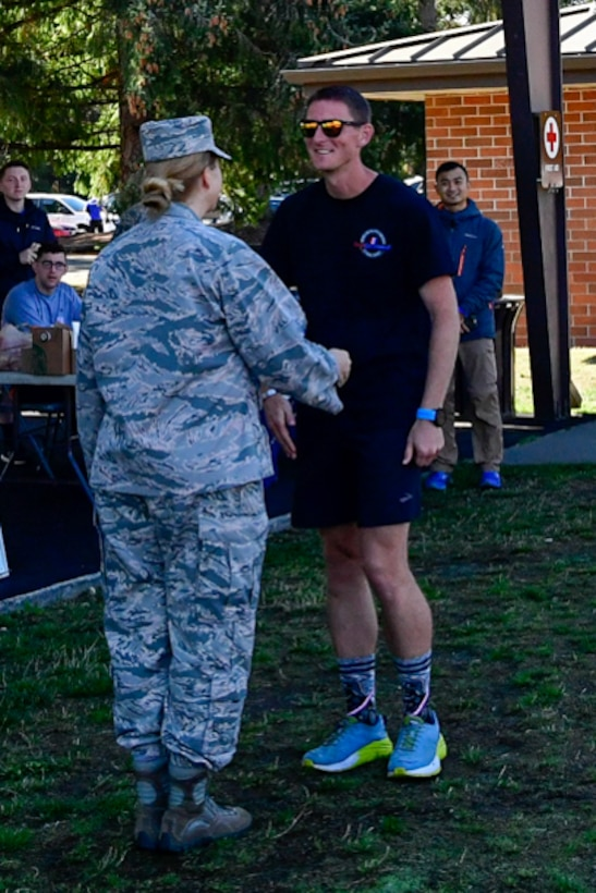 1st Lt. Krosby Keller, right, 225th Air Defense Squadron air battle manager, receives a commander's coin from Col. Erin Staine-Pyne, 62nd Airlift Wing vice commander, for placing first in the individual standings during the Joint Base Lewis-McChord 24-Hour POW/MIA Remembrance Run Sept. 19, 2018.  Keller logged in 100 miles in under 24 hours. (U.S. Air National Guard photo by Maj. Kimberly Burke)