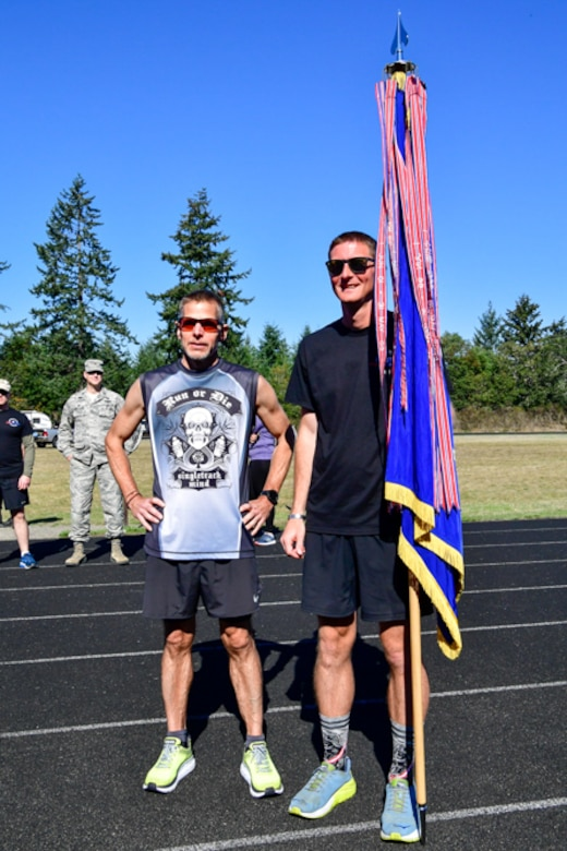 Bruce Robie, left, 225th Support Squadron National Airspace System Defense program manager, and 1st Lt. Krosby Keller, right, 225th Air Defense Squadron air battle manager, proudly hold the Western Air Defense Sector colors after completing 174 miles between them during the Joint Base Lewis-McChord 24-Hour POW/MIA Remembrance Run Sept. 19, 2018.  Keller placed first in individual standings with 100 miles and Robie finished second with 74 miles. (U.S. Air National Guard photo by Maj. Kimberly Burke)