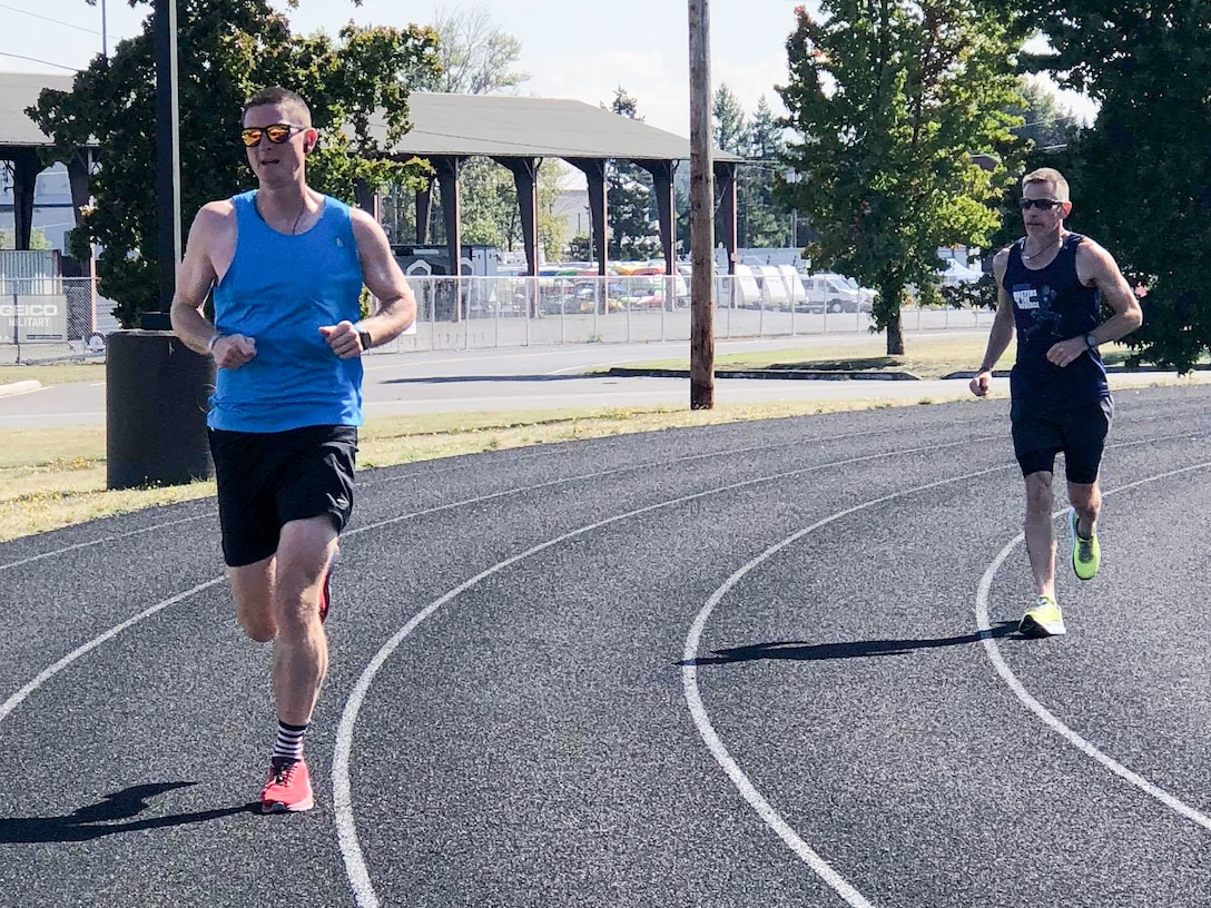 1st Lt. Krosby Keller, left, 225th Air Defense Squadron air battle manager, runs with Bruce Robie, right, 225th Support Squadron National Airspace System Defense program manager, during the Joint Base Lewis-McChord 24-Hour POW/MIA Remembrance Run Sept. 18, 2018.  Keller placed first in individual standings with 100 miles and Robie finished second in the individual standing with 74 miles.