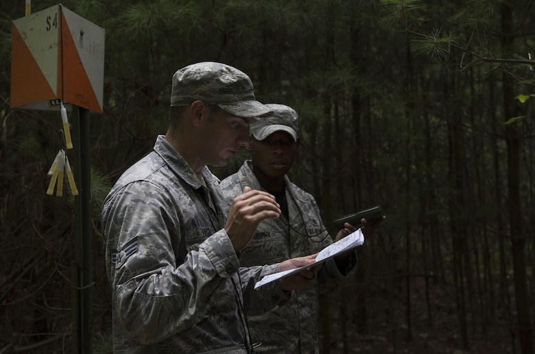 Senior Airman Joseph Pace, Fairchild Air Force Base, Washington, 92nd Security Forces Squadron installation patrolman, and U.S. Air Force Staff Sgt. Bryan Murphy, Joint Base McGuire-Dix-Lakehurst, New Jersey, 421st Combat Training Squadron Phoenix Raven instructor, navigate the woods using a map and GPS during land navigation training on Joint Base McGuire-Dix-Lakehurst, New Jersey, in preparation for representing Air Mobility Command in the 2018 Air Force Defender Challenge Sept. 7, 2018. Teams were instructed to find specific marked points using only a map and GPS to find their way.