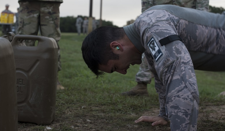 Senior Airman Anthony Hu, 6th Security Forces Squadron military working dog handler and Air Mobility Command team member, performs pushups during the 2018 Air Force Defender Challenge on Joint Base San Antonio-Camp Bullis, Texas, Sept. 13, 2018. Hu performed the last exercise of the combat endurance test on the last day of the three-day competition. (U.S. Air Force photo by Airman Ariel Owings)
