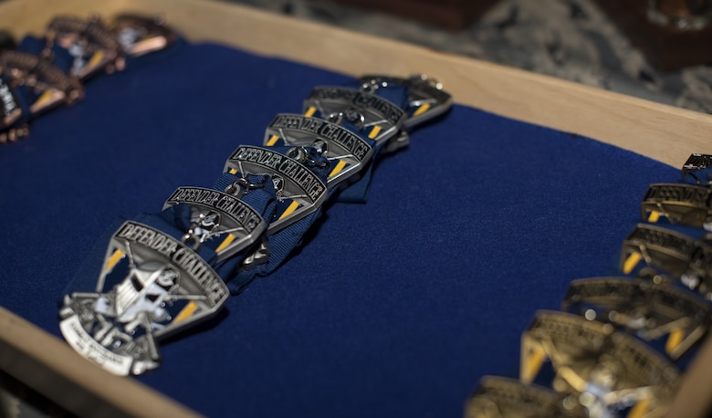 Medals sit in a tray during the 2018 Air Force Defender Challenge award ceremony on Joint Base San Antonio-Camp Bullis, Texas, Sept. 13, 2018. Gold, silver and bronze coins were awarded to place winners in the competition. The competition was comprised of weapons scenarios, dismounted operations and combat endurance. (U.S. Air Force photo by Airman Ariel Owings)
