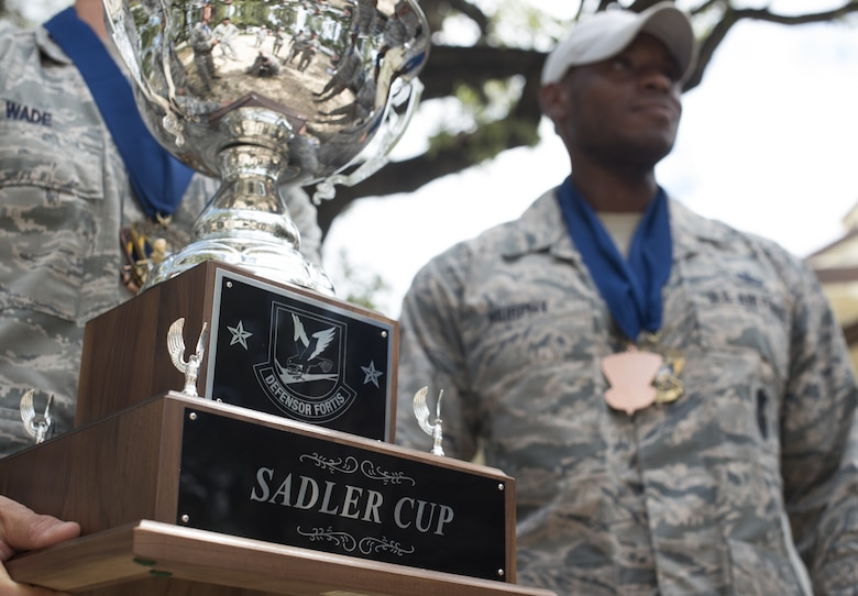 Air Mobility Command security forces Airmen hold the Sadler Cup after the 2018 Air Force Defender Challenge award ceremony on Joint Base San Antonio-Camp Bullis, Texas, Sept. 13, 2018. The Sadler Cup was awarded to the AMC team for placing first in the dismounted operations component of the three-day competition. (U.S. Air Force photo by Airman Ariel Owings)
