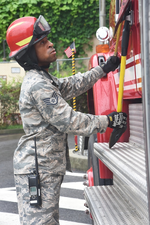 U.S Staff Sgt. Devon Smith, firefighter with the 51st Civil Engineer Squadron fire department, secures the driver door with axes during a mass casualty exercise at Osan Air Base, Republic of Korea, Sept. 20, 2018. The firefighters conducted high angle rescue training to better familiarize themselves with saving the lives of trapped victims using rope rescue. (U.S. Air Force photo by Tech. Sgt. Ashley Tyler)