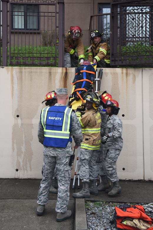Firefighters with the 51st Civil Engineer Squadron fire department evacuate a simulated victim from a burning building during a mass casualty exercise at Osan Air Base, Republic of Korea, Sept. 20, 2018. The fire department worked closely with the 51st Medical Group field response team to evaluate high angle rescue operations, patient treatment and packaging and receiving patients for transport to a medical facility. (U.S. Air Force photo by Tech. Sgt. Ashley Tyler)