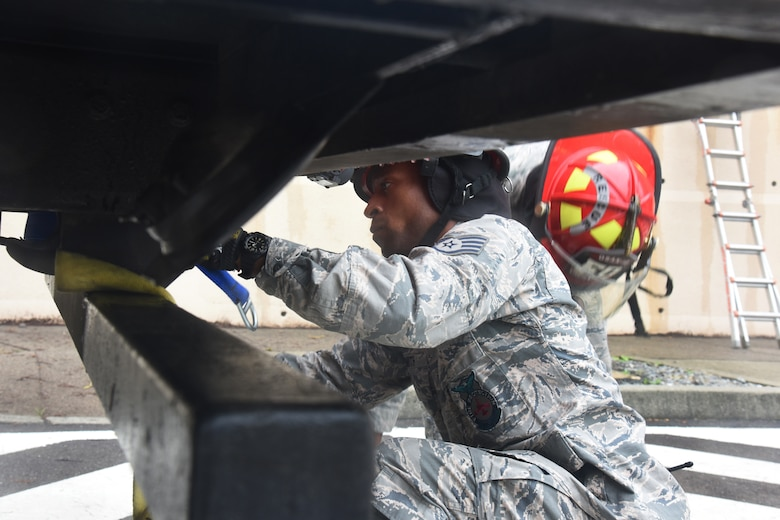 U.S Staff Sgt. Devon Smith, firefighter with the 51st Civil Engineer Squadron fire department, wraps a cord around the edge of a fire truck during a mass casualty exercise at Osan Air Base, Republic of Korea, Sept. 20, 2018. The firefighters used the cord to raise and lower a stretcher to rescue a simulated victim out of a burining building. (U.S. Air Force photo by Tech. Sgt. Ashley Tyler)