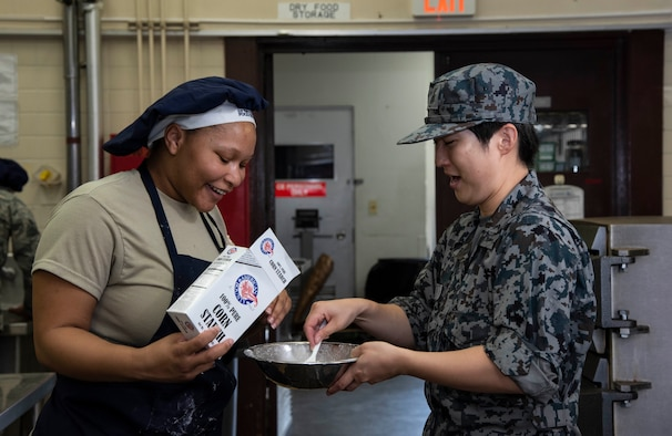 U.S. Air Force Airman 1st Class Ty'Lacia Berard, a 35th Force Support Squadron food specialist, helps Japan Air Self-Defense Force Tech. Sgt. Tomoyo Kato, a 27th Aircraft Control and Warning Squadron nutritionist, create a corn starch mix during a Bilateral Exchange Program visit at Misawa Air Base, Japan, Sept. 21, 2018. Kato learned how to make larger portions of meals for thousands of Airmen, whereas she normally only makes meals for approximately 300 personnel at her unit. (U.S. Air Force  photo by Senior Airman Sadie Colbert)