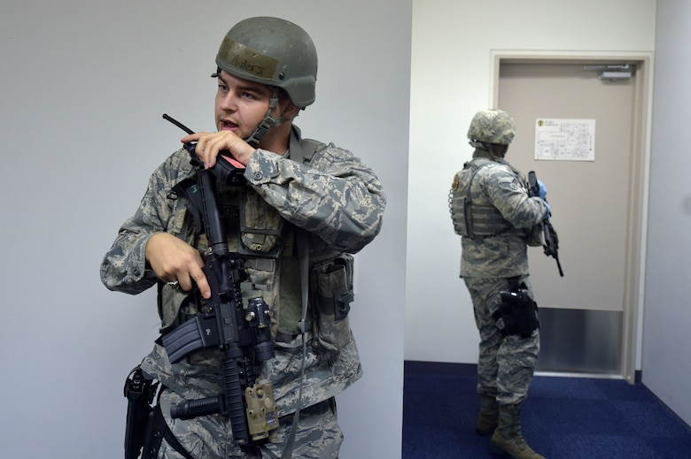 U.S. Air Force Senior Airman Daniel Anders, left, a 35th Security Forces Squadron defender, talks on a radio during an active shooter exercise at Misawa Air Base, Sept. 18, 2018. The exercise helped security forces personnel identify any short falls or limiting factors in their response capabilities. This aids in providing an effective and timely response to minimize the loss of life in the event of an active shooter. (U.S. Air Force photo by Tech. Sgt. Stephany Johnson)