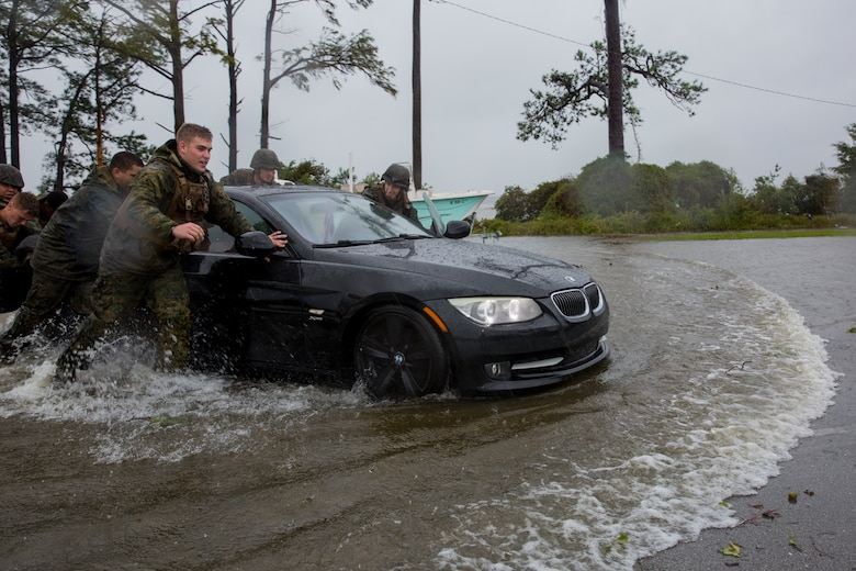 Marines with Marine Corps Base Camp Lejeune help push a car out of a flooded area during Hurricane Florence, on Marine Corps Base Camp Lejeune, Sept. 15, 2018. Hurricane Florence impacted MCB Camp Lejeune and Marine Corps Air Station New River with periods of strong winds, heavy rains, flooding of urban and low lying areas, flash floods and coastal storm surges. (U.S. Marine Corps photo by Lance Cpl. Isaiah Gomez)
